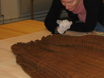 Archaeologist Ulla Mannering studying the skirt in the laboratory. (Photo: Colourbox)