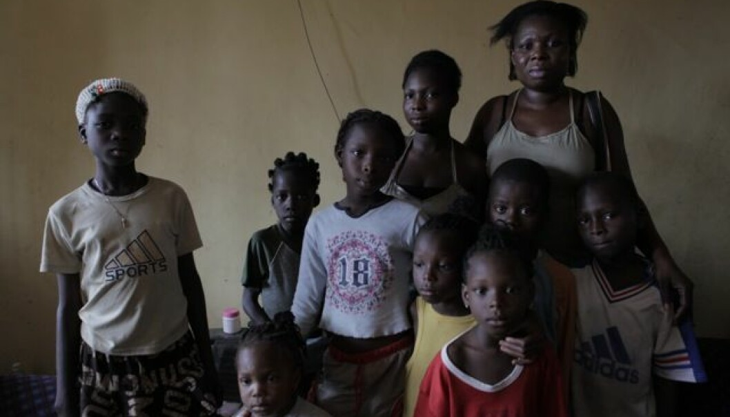 """Upon their return from Europe, Nigerian victims of sex trafficking suddenly end up being responsible for taking care of their relatives, because it's assumed that they have made lots of money up there. Pictured is one of the repatriated women, """"Esther"""", with her five children and four other children in her family. (Photo: Janus Metz)"""