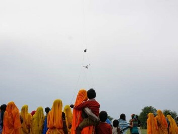 Local spectators watch on as a helicopter equipped with a new Danish airborne surveying technique goes on the lookout for fresh drinking water in India. (Photo: Esben Auken)