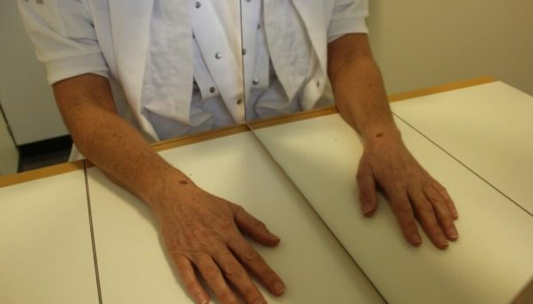 An occupational therapist demonstrates the principle of mirror therapy: the mirror is positioned so that the existing arm is reflected in the mirror. Here, some patients will find that their phantom arm merges with the arm they see in the mirror, and this can relieve the phantom pains. In a new study, researcher Bo Geng aims to further develop this form of treatment, while at the same time stimulating the stump of the amputated limb with tiny electrical shocks. (Photo: Lise Brix)