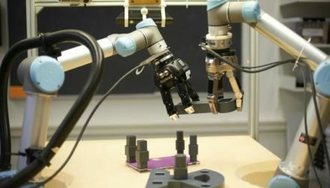 The two robotic arms work in tandem to build a pendulum from the objects on the table. (Photo: University of Southern Denmark)