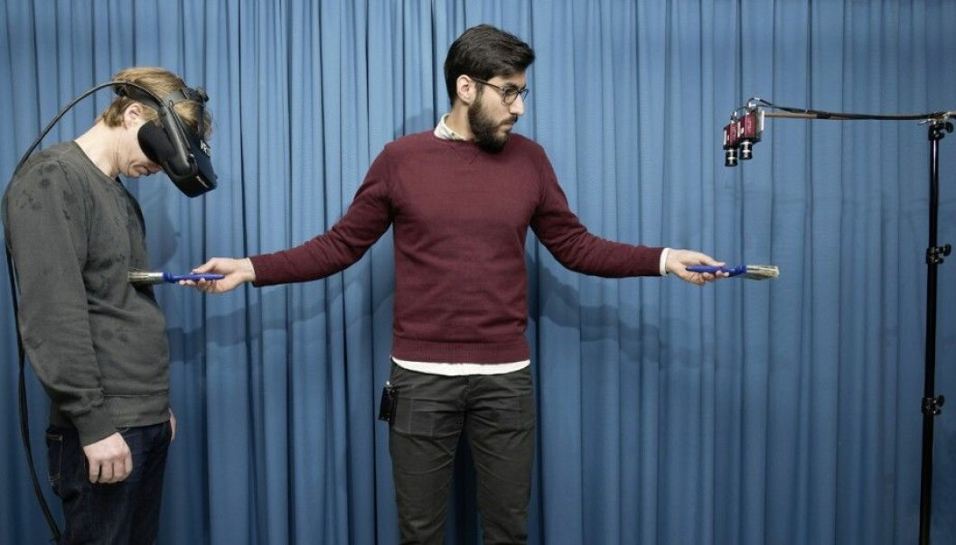 Researcher Zakaryah creates the illusion of an invisible body for the test person on the left. The participant is wearing virtual reality goggles which produce images in 3D that are projected by the camera on the right. The experimenter triggers the illusion by touching the test person with a brush. He simultaneously moves another brush, picked up by the camera, in corresponding spots. (Photo: Staffan Larsson)
