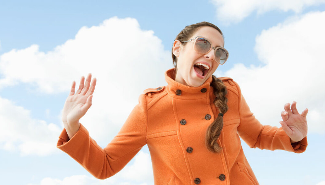 """People who score high on extraversion are emotionally warm, participating, chatty, active, pleasure-seeking and passionate. The low-scoring introverted individuals are conversely reserved, introverted, quiet, serious and emotionally subdued. (Photo: <a href=""""http://www.shutterstock.com/pic-145913753/stock-photo-attractive-quirky-individual-woman-shouting-and-holding-her-arms-in-the-air-with-a-humorous-fun.html"""" target=""""_blank"""">Shutterstock</a>)."""