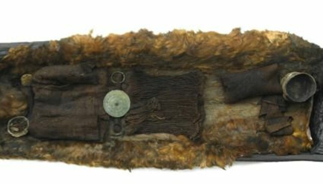 The Egtved Girl's oak coffin shown along with a well-preserved wool garment and a bronze belt decorated with small spirals. (Photo: Roberto Fortuna, National Museum of Denmark)