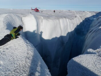 A monster moulin on the Russell Glacier, Greenland. You can see a helicopter for scale. These large gaping holes allow rain and melt water to drain quickly into the ice sheet. (Photo: Alun Hubbard)