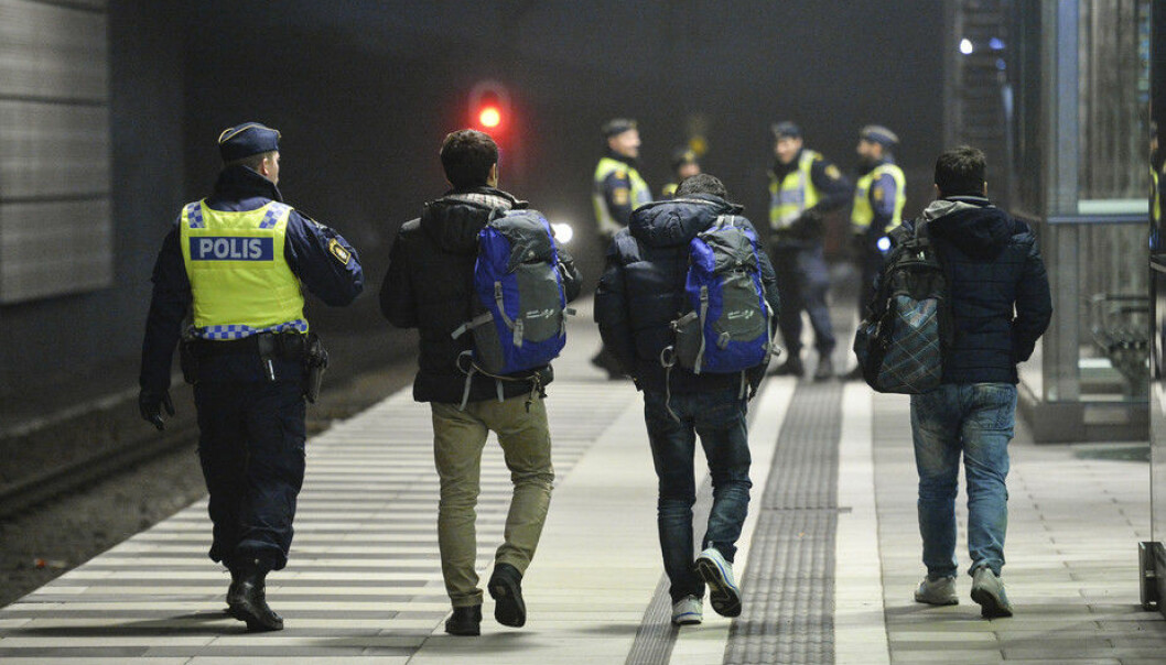 A police officer escorts migrants from a train at Hyllie station outside Malmo. (Photo: TT News Agency/Reuters)
