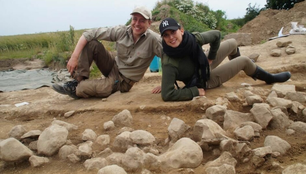 Archaeologists pose behind the newly discovered cup marked petroglyphs (the stones with rounded indents) on the Danish island Bornholm. (Photo: Melissa Cherry Villumsen, archaeology student at the University of Copenhagen, Denmark)